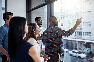 Buy stock photo Shot of a young businessman giving a demonstration on a glass wall to his colleagues in a modern office