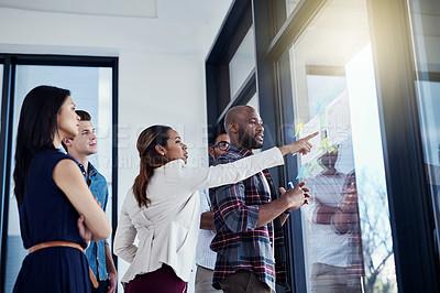 Buy stock photo Shot of a young businesswoman giving a demonstration on a glass wall to her colleagues in a modern office