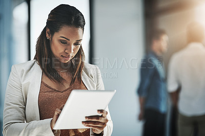 Buy stock photo Shot of a young businesswoman using her digital tablet in a modern office with her colleagues in the background
