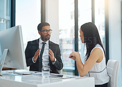 Buy stock photo Cropped shot of two businesspeople having a discussion in a modern office