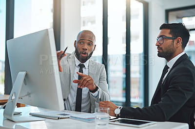 Buy stock photo Cropped shot of two businessmen working together on a computer in a modern office