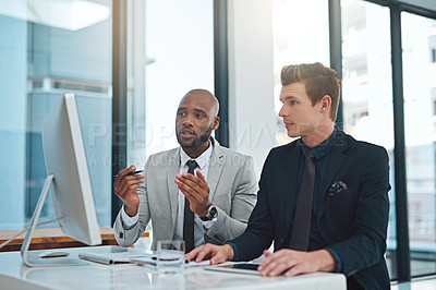 Buy stock photo Cropped shot of two young businessmen having a discussion while working on a computer in a modern office