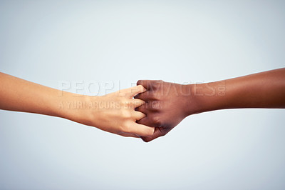 Buy stock photo Cropped studio shot of two women joining their hands against a gray background