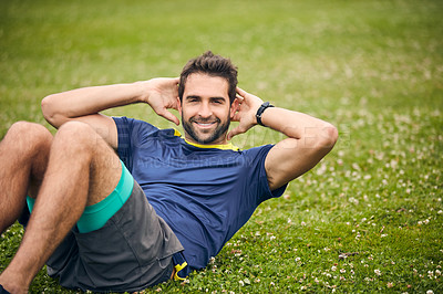 Buy stock photo Shot of a sporty man doing sit-ups