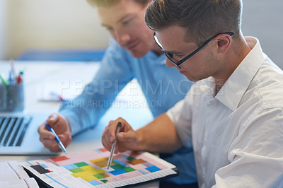 Buy stock photo Shot of two handsome young businessmen working together in their office