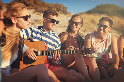 Buy stock photo Cropped shot of a handsome young man playing a guitar for his friends on a summer's day at the beach
