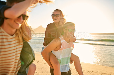 Buy stock photo Cropped shot of two affectionate young men piggybacking their girlfriends at the beach