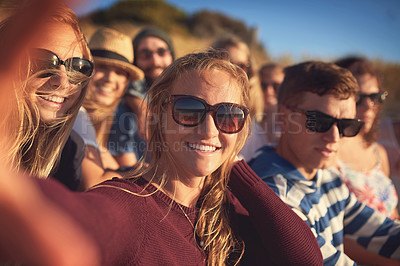 Buy stock photo Cropped portrait of an attractive young woman taking a selfie with her friends at the beach