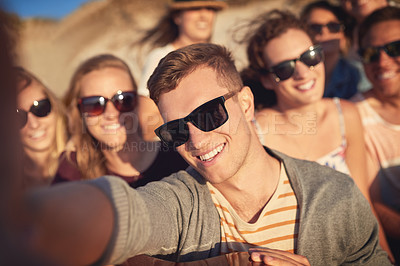 Buy stock photo Cropped portrait of a young man taking a selfie with his friends at the beach