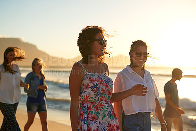 Buy stock photo Cropped shot of two young women walking with their friends at the beach