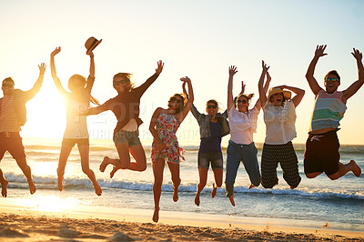 Buy stock photo Full length shot of a group of friends jumping into mid air at the beach