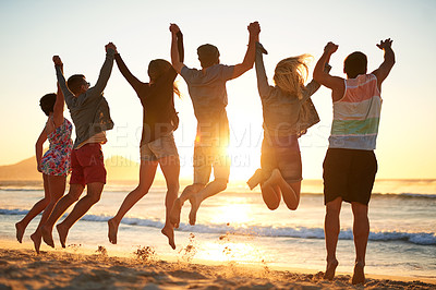 Buy stock photo Rearview shot of a group of young friends jumping into the air while holding hands at the beach
