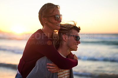 Buy stock photo Cropped shot of an affectionate young man piggybacking his girlfriend on the beach