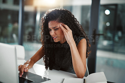 Buy stock photo Shot of a young businesswoman looking stressed out while working late on a laptop in an office
