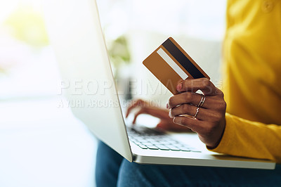 Buy stock photo Cropped shot of a young woman using a laptop and a credit card while relaxing at home