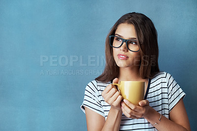 Buy stock photo Studio shot of an attractive young woman having a beverage and looking thoughtful against a blue background