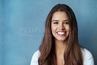 Buy stock photo Studio shot of an attractive young woman posing against a blue background