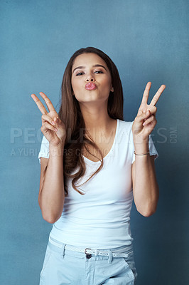 Buy stock photo Studio shot of an attractive young woman making a peace gesture against a blue background