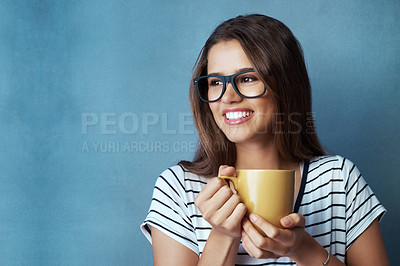 Buy stock photo Studio shot of an attractive young woman having a beverage against a blue background