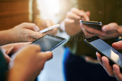 Buy stock photo Cropped shot of a group of colleagues using their smart phones in synchronicity