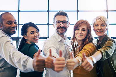 Buy stock photo Cropped portrait of a team of colleagues giving a thumbs up in a modern office