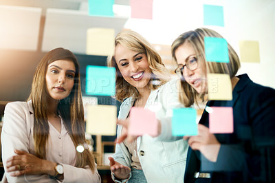 Buy stock photo Shot of a group of businesswomen arranging sticky notes on a glass wall in a modern office