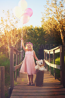 Buy stock photo Shot of a happy little girl holding balloons and a teddy bear while standing in the middle of a bridge