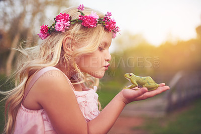 Buy stock photo Shot of a cheerful little girl holding a frog and going in for a kiss while standing outside in nature