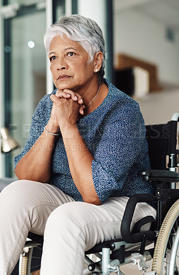 Buy stock photo Shot of a relaxed elderly woman seated in a wheelchair while contemplating at home during the day