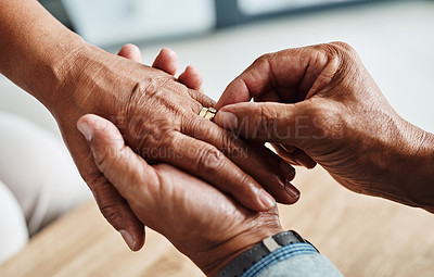Buy stock photo Shot of an unrecognizable person's hand being held by another person in comfort while putting a ring on the finger during the day