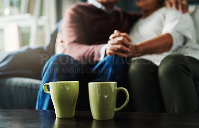 Buy stock photo Shot of an unrecognizable elderly couple holding hands and drinking coffee while being seated on a couch at home