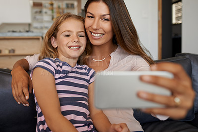 Buy stock photo Shot of a mother and her little daughter taking selfies together at home