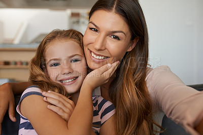 Buy stock photo Portrait of a mother and her little daughter taking selfies together at home