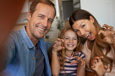 Buy stock photo Portrait of a little girl and her parents taking selfies together at home