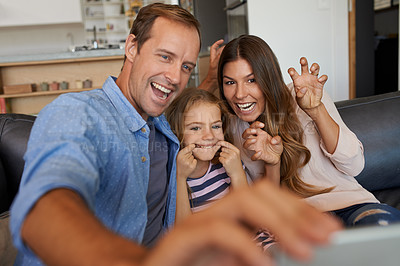 Buy stock photo Shot of a little girl and her parents taking selfies together at home