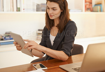 Buy stock photo Shot of a young woman using a digital tablet while working from home
