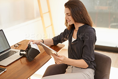 Buy stock photo Shot of a young woman using a digital tablet and a virtual reality headset while working from home