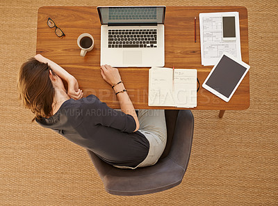 Buy stock photo High angle shot of a young woman looking tired while working in her home office