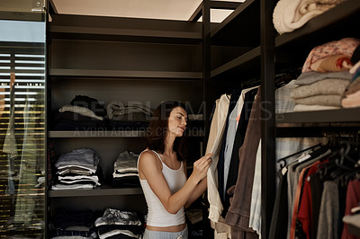 Buy stock photo Shot of a beautiful young woman choosing clothes from her closet in the morning at home