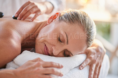 Buy stock photo Shot of a mature woman getting a hot stone massage at a spa