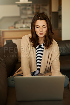 Buy stock photo Shot of a beautiful young woman using a laptop at home