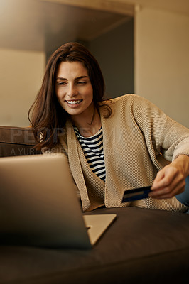 Buy stock photo Shot of a beautiful young woman using a laptop and credit card at home