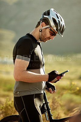 Buy stock photo Shot of a mature man using a mobile phone while out for a ride on his mountain bike