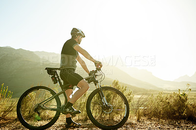 Buy stock photo Shot of a mature man taking a break while out for a ride on his mountain bike