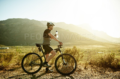 Buy stock photo Shot of a mature man having a water break while out for a ride on his mountain bike