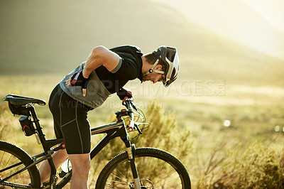 Buy stock photo Shot of a mature man experiencing back pain while out for a ride on his mountain bike