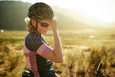 Buy stock photo Shot of a sporty woman suffering from a headache while out cycling