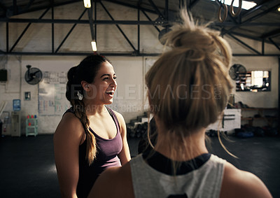 Buy stock photo Cropped shot of two attractive young women working out in the gym