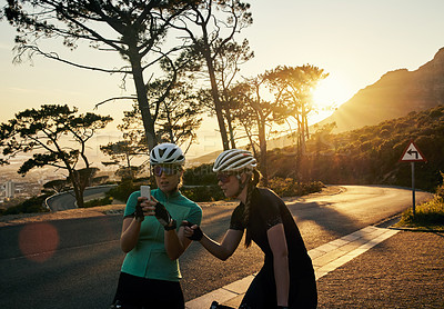 Buy stock photo Shot of two sporty young women using a cellphone together while out cycling