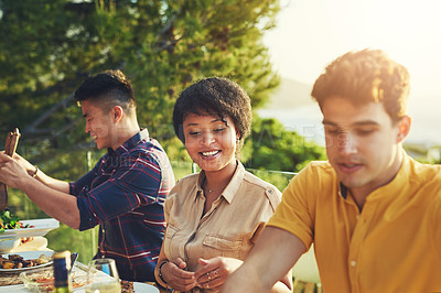Buy stock photo Shot of a group of friends enjoying a meal and drinks together around a table at a gathering outdoors